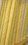 Quilt Fabric. Bolts of yellow quilt fabric in various patterns on shelves and read to purchase stock photo