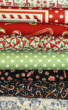 Quilt Fabric. Bolts of Christmas Quilt Fabric Candy Canes peppermints bright designs snow scene holidays ribbons royalty free stock photo