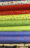 Quilt Fabric. Bolts of bright christmas quilt fabric with tree lights, red ornaments, blue, packages, festive, holiday Royalty Free Stock Photos