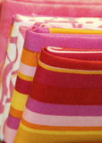 Quilt Fabric. On bolts in bright pinks, and colorful yellows, reds and white stock images