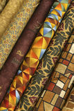 Quilt Fabric. Fabric Bolts of quilt fabric in various designs in brown, yellow, orange, blue, beige and burgundy colors royalty free stock photo