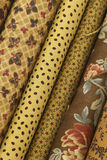 Quilt Fabric. Fabric Bolts of quilt fabric in browns beige yellow amber in various designs including flowers dots stars and leaves royalty free stock photography