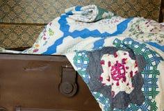 Quilt handmade do vintage que encontra-se em um tronco velho. Imagem de Stock