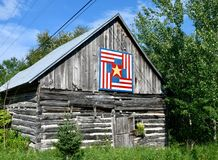 Quilt Pattern on Log Farm Building. This is a Summer picture of an old dilapidated log farm building with a quilt pattern displayed on it in Door Coumty royalty free stock photography
