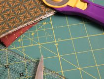 Quilt rotary cutting mat with fabric in background Stock Image