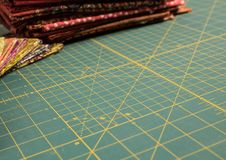 Quilt rotary cutting mat with multicolored fabric in background Stock Images