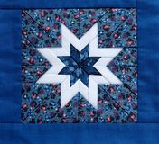 Quilt star blue. Quilted star in white with colorful fabrics and a blue border Stock Photography