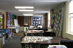 The Quilt Workroom. Interior of quilting workroom, including quilting and sewing machine rooms and sample quilts stock image