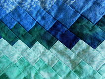 Quilted Background. Quilted pieces of fabric in beautiful different shades of blue and green colors Stock Photo