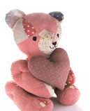 Quilted bear with calico heart. Teddy bear made from antique quilts holding a large mauve calico heart Royalty Free Stock Photos