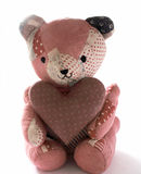 Quilted bear wit calico heart. Teddy bear made from antique quilts holding a large mauve calico heart Stock Images