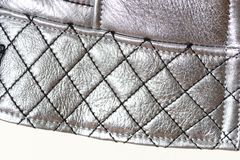Quilted edge of the twist with seams in the form of a grid, background. Silver color of clothes. Macro. Quilted edge of the twist with seams in the form of a royalty free stock photos