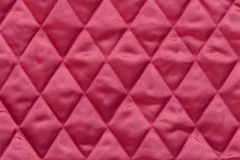 Quilted red satin fabric. Close up of quilted christmas tree skirt fabric in traditional red color Stock Photography