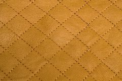 Quilted yellow with gold leather texture. Or background, closeup view stock photos