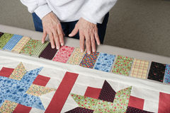 Quilter arranging piano key border. A quilter arranges fabric to assemble a piano key border to finish a quilt top Stock Photo