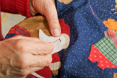 Quilter completing a french knot. A quilter finishing a french knot on an applique pattern Stock Photography