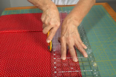 A quilter cuts fabric for quilt making. A woman cuts colorful red fabric with a rotary cutter for use in a new quilt Stock Image