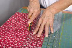 A quilter cuts fabric for quilt making. A woman cuts colorful red fabric with a rotary cutter for use in a new quilt Royalty Free Stock Photo