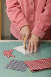 Quilter cutting fabric. A quilter cuts 4 squares of fabric into triangles for a quilt top Royalty Free Stock Photography