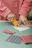 Quilter cutting fabric. A quilter cuts 4squares into triangles using a rotary cutter Royalty Free Stock Photography