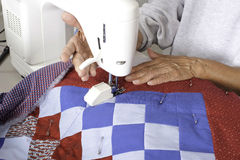 A quilter lifting a walking foot off of the quilt. A female quilter lifting the walking foot lever after completing the grid pattern on a patriotic quilt Stock Image