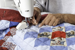 A quilter machine quilting patriotic quilt. A female quilter finishes grid pattern on a patriotic quilt Stock Image