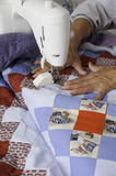Quilter machine quilting patriotic quilt. A quilter quilting/sewing a grid pattern to complete a patriotic quilt Stock Photo