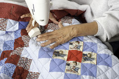 A quilter machine quilting patriotic quilt. A woman machine quilting/sewing three layers to create a grid pattern on a patriotic quilt Stock Photography