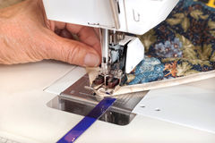 Quilter sewing on binding to quilt. A quilter guides binding material through the walking foot of a sewing machine Stock Photos