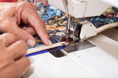 Quilter sewing on binding to quilt. Royalty Free Stock Photo