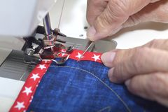 Completing mitered corner of a quilt. A quilter sewing down binding to finished quilt Royalty Free Stock Photo