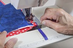 Sewing down binding. A quilter sewing down binding to finished quilt Stock Images