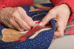 Quilter stitching quilt. A quilter works on stitching fabric on a quilt Stock Images