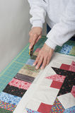 Quilter trimming  piano keys of quilt top fabric. Quilter cutting excess fabric off of  piano key border Royalty Free Stock Image