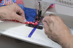 Completing mitered corner of a quilt. A quilter uses a stihletto to guide the fabric to complete a mitered corner on a quilt Royalty Free Stock Photos