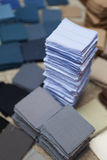 Quilting Blocks. Blocks of fabric stacked by color, with one stack much taller than the others. Fabric blocks are mostly somber shades of blue, gray and brown Royalty Free Stock Image
