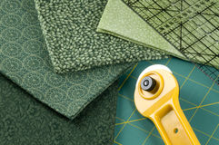 Quilting in green. Quilting supplies: green materials, rotary cutter, pad and ruler Royalty Free Stock Images