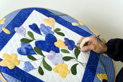 Quilting on hoop. A woman works on a hand quilted quilt using a hoop Royalty Free Stock Photography
