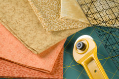 Quilting in Orange. Quilting supplies: orange materials, rotary cutter, pad and ruler Stock Images