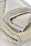 Quilts. Folded textured quits and throws in neutral earth tones Stock Images