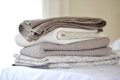 Quilts. Folded textured quits and throws in neutral earth tones Stock Image