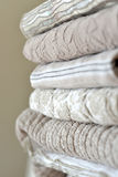 Quilts. Folded textured quits and throws in neutral earth tones Stock Photo