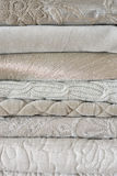 Quilts. Folded textured quits and throws in neutral earth tones Royalty Free Stock Image