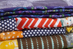 Quilts Stacked Up. A close up of stacked quilts showing different patterns and cloth texture Royalty Free Stock Images