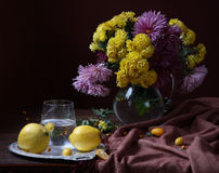 Quince and bouquet from asters. Still-life with a quince and a magnificent bouquet in a transparent jug stock photo