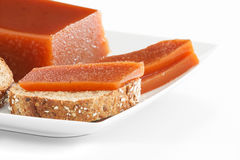 Quince jam on bread. Detail of quince marmalade slices on seeds bread on a plate over white brackground Stock Image