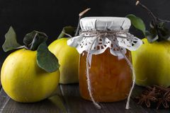 Quince jam in glass jar  and fresh quince. With leaves, selective focus on dark wooden table Royalty Free Stock Photo