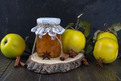 Quince jam in glass jar  and fresh quince. With leaves, selective focus on dark wooden table Royalty Free Stock Photography