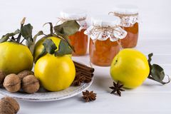 Quince jam in glass jar  and fresh quince. With leaves, selective focus on white wooden table Stock Photography