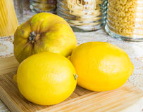 Quince and two lemons on a wooden board and jars on the background Stock Images